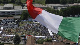 A man waves the Italian flag on a hill during a the traditional League party rally in Pontida in 2018.
