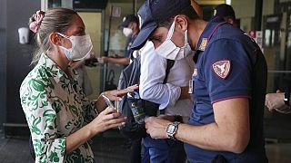 Olasz nő védettségi igazolványát ellenőrzik