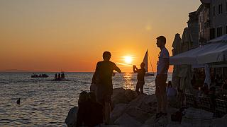 Holidaymakers enjoy the sunset on the seafront in the Adriatic town of Rovinj, Croatia, Friday, Aug. 27, 2021