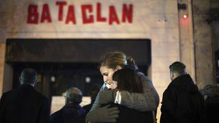 Women hug in front of the Bataclan concert hall in Paris, as France marked the anniversary of Islamic extremists' coordinated attacks on Paris, Nov. 13, 2016.