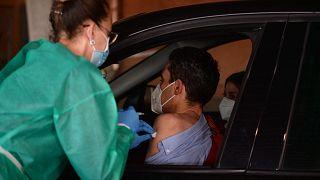 عامل صحي يعطي جرعة من لقاح أسترازينيكا / أكسفورد لرجل في سيارة في مركز تطعيم ضد فيروس كورونا في ملعب نويفو كولومبينو، إسبانيا، 24 مارس 2021