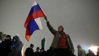 FILE - In this Sept. 20, 2021 file photo, a demonstrator holds a Russian national flag during a protest against the results of the Parliamentary election in Moscow, Russia.