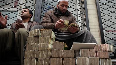 An Afghan money changer, right, counts a pile of currency. Cryptocurrencies, on the other hand, have been a financial lifeline for many Afghans