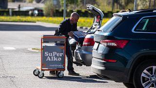 A shopper loads his car at a alcohol shop near the Latvian-Estonian border