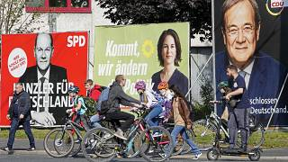 People walk and drive past election posters of the three German chancellor candidates.