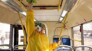 عامل يعقم حافلة للنقل العام بموسكو في آذار/مارس 2020