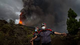 A police officer orders journalists to leave the area during a media tour near the volcano on the island of La Palma in the Canaries, Spain, Sept. 22, 2021.