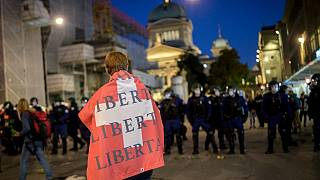 """A man holding a Swiss flag on his shoulders reading """"Freedom"""" walks past riot police."""