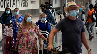 Passengers arrive at Terminal 5 of Heathrow Airport in London, Monday, Aug. 2, 2021