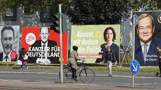 People walk and drive past election posters of the three chancellor candidates in Gelsenkirchen, Germany, Sept. 23, 2021.