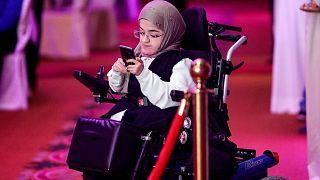 فتاة كويتية من ذوي الاحتياجات الخاصة تنظر إلى هاتفها الخلوي خلال نشاط لذوي الاحتياجات الخاصة في مدينة الكويت، 28 أبريل 2018.
