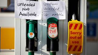 Hand written signs are stuck to a petrol pump with no fuel available at a Shell filling station in Manchester