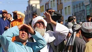 Menschen in Herat in Afghanistan blicken auf die an einem Kran hängenden Gehängten
