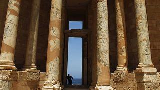 رجل ليبي يتكئ على جزء من المدرج الروماني في موقع صبراتة الأثري في ليبيا