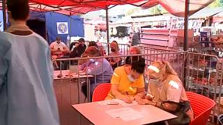 People filling in documents prior to vaccination in a Bucharest square