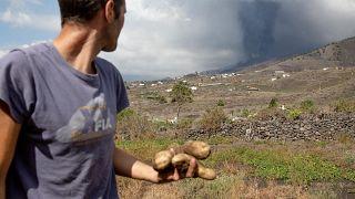 Ein Bauer blickt auf die Rauchsäule des Vulkans