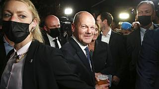 Olaf Scholz, center, Finance Minister and SPD candidate for Chancellor, drinks a beer as he leaves the election party at Willy Brandt House in Berlin