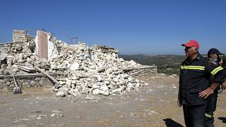 Firefighters stand next to a demolished Greek Orthodox church of Profitis Ilias after a strong earthquake in Arkalochori, on the island of Crete, Greece, Sept. 27, 2021.