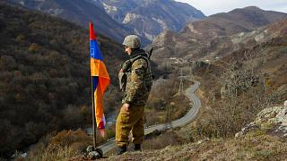 An ethnic Armenian soldier stands guard next to Nagorno-Karabakh's flag