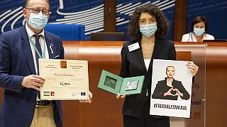 Parliamentary Assembly Rik Daems, left, holds a diploma while Tatiana Khomich holds a poster of jailed Belarus civil rights activist Maria Kalesnikava.