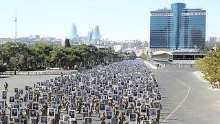 جنود أذربيجانيون في مسيرة بالعاصمة باكو الاثنين ٢٧ أيلول/سبتمبر 2021 يحملون صور القتلى الذي قضوا في القتال مع الجيش الأرميني للسيطرة على ناغورني  قره باغ قبل عام