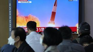 People watch a TV showing a file image of North Korea's missile launch during a news program at the Seoul Railway Station in Seoul, South Korea, Sept. 28, 2021.