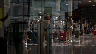 مسافرون في مطار برشلونة، إسبانيا.