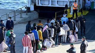 Migrants queue before boarding the GNV Azzurra ship after being transferred from the migrant centre on the Sicilian island of Lampedusa, May 13, 2021.