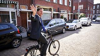 Netherlands Prime Minister Mark Rutte leaves on his bike after voting in the European elections in The Hague, Netherlands, Thursday, May 23, 2019