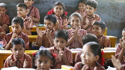A group of children smile as they learn in a classroom.