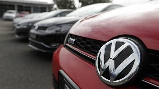 Display cars are parked at a Volkswagen dealership.