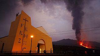 Una persona contempla la erupción del volcán Cumbre Vieja desde la puerta de una Iglesia en la isla española de La Palma