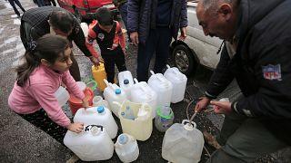 أشخاص يملأون أوعية بلاستيكية بمياه من صنبور ماء في دمشق، سوريا ، الاثنين ، 16 يناير / كانون الثاني 2017.