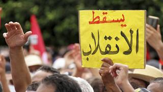 """متظاهر يحمل لافتة  كتب عليها """"يسقط الانقلاب"""" خلال مظاهرة ضد الرئيس التونسي قيس سعيد في العاصمة تونس الأحد 26 أيلول/ سبتمبر 2021"""