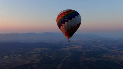 A hot air balloon soars above the Tuscan countryside