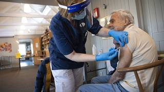 A health worker administers a Pfizer's COVID-19 vaccine to a man at a temporary vaccination clinic in a church in Sollentuna, Sweden, Tuesday March 2, 2021.