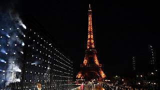 Models presenting creations by Saint Laurent with the Eiffel tower in the background during the Paris Fashion Week on September 28, 2021.