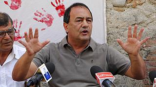 """In this photo taken on Sept. 2019, the former mayor of Riace, in Southern Italy, Domenico """"Mimmo"""" Lucano receives media attention."""