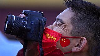 """Un hombre luce una mascarilla con el lema """"amo China"""" mientras fotografía el izado de bandera. Pekín, China 1/10/2021"""