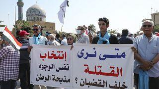 عراقيون يحملون لافتات أثناء مظاهرة في ساحة الفردوس وسط بغداد في 1 تشرين الأول 2021.