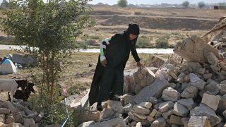امرأة تمشى على أنقاض بيتها المهدم بسبب الزلزال في سربول الذهب غربي إيران. 2017/11/15