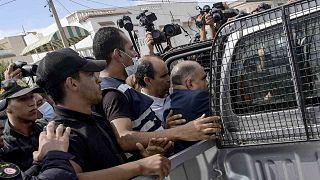 عناصر قوات الأمن يحمون محمد القوماني، النائب التونسي وعضو حركة النهضة، بعد أن هاجمه مواطنون أمام مقر البرلمان، العاصمة تونس، 1 أكتوبر 2021