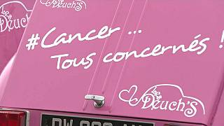 """A French charity undertaking a road trip through the country to spread awareness uses pink 2CVs reading """"#Cancer... Tous concernés!"""" (#AllConcerned)."""
