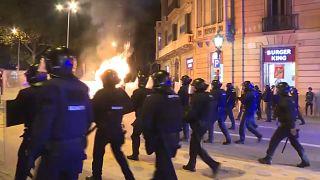 Un grupo de agentes antidisturbios avanza hacia una zona en la que varios individuos están quemando contenedores