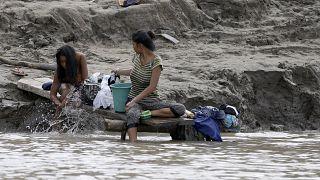 سيدتان تجلسان على نهر أمازون حيث تلتقي حدود البراويل وبيرو وكولومبيا. 08/09/2019