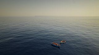 """مهاجرون بانتظار سفينة الإنقاذ """"أوبن آرمز"""" على بعد 20 ميلاً من السواحل الإيطالية (تموز-يوليو 2021)"""