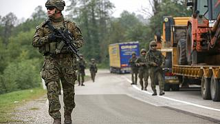 Polish soldiers, part of the peacekeeping mission in Kosovo KFOR, pass through barricades as they patrol near the crossing at Jarinje, Kosovo-Serbia border, October 2, 2021.