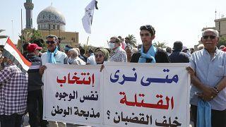 عراقيون يحملون لافتات أثناء تجمعهم في ساحة الفردوس وسط بغداد. 2021/10/01