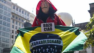 """Manifestant tenant un drapeau brésilien où est écrit """"Bolsonaro dehors"""" - Rio de Janeiro, le 02/10/2021"""
