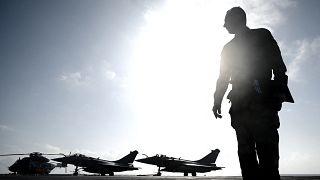 عسكري أمام مقاتلات رافال فوق حاملة طائرات شارل ديغول في عرض ساحل مدينة هير الفرنسية. 2020/01/23